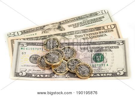 British pound coins on US Dollar Bills with white background