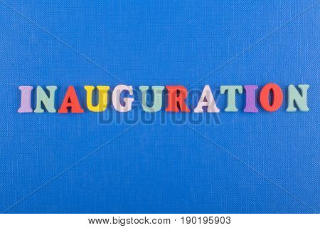 Iinauguration . English word on blue background composed from colorful abc alphabet block wooden letters, copy space for ad text. Learning english concept