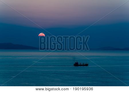 Ship Passing The Setting Sun