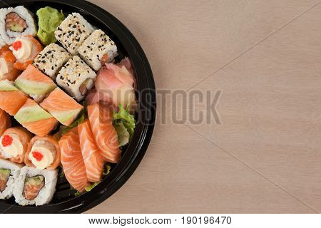 Set of assorted sushi kept in a black round box against white background