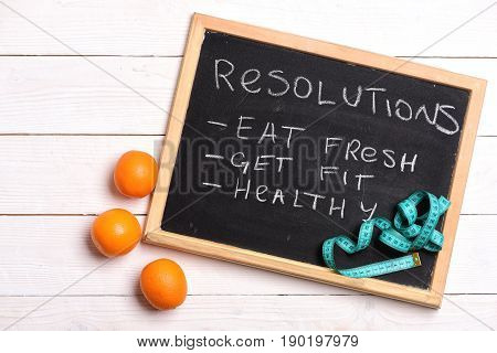 Diet on chalkboard. List of resolutions for healthy life with handwritten phrases like eat fresh get fit and healthy near orange fruit and cyan measuring tape on white wood background top view