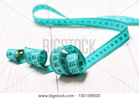 Roll of measuring tape in cyan colour lying on white wooden background close up and selective focus. Vintage measurement tool