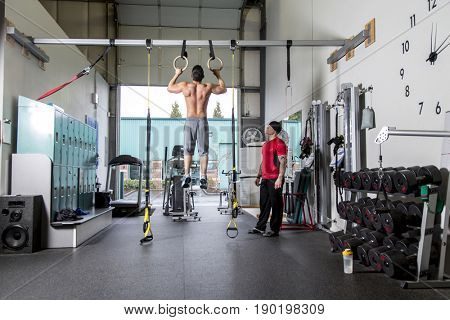 Man working with trainer in gym