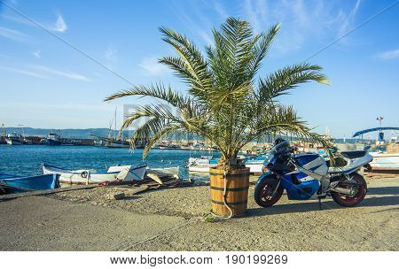 picturesque view on a small bay gulf at Black sea coast with palm and vivid motobike. Nesebar Bulgaria