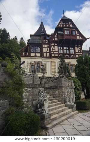 close view at part the Peles Castle Sinaia Romania Europe. with stairs between two statues of lions and cannons