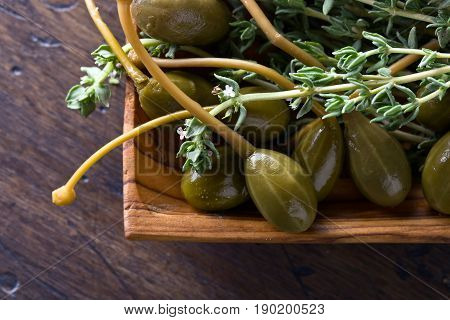 Canned capers and branches of thyme on a wooden table .Top view.