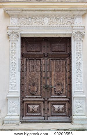 one of the ancient door with wood carving at medieval Peles Castle Romania. front view