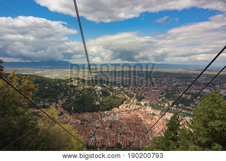 the ropeway with overlooking in distance medieval architecture of the old European city Brasov Romania