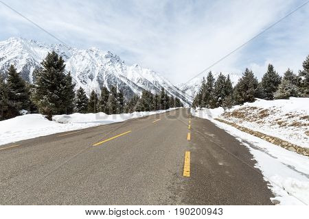 empty asphalt road with snow mountain in tibet plateau