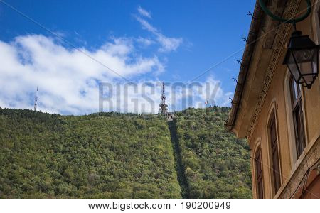 the green mountain with ropeway and facade building with lantern at old european town Brasov Romania