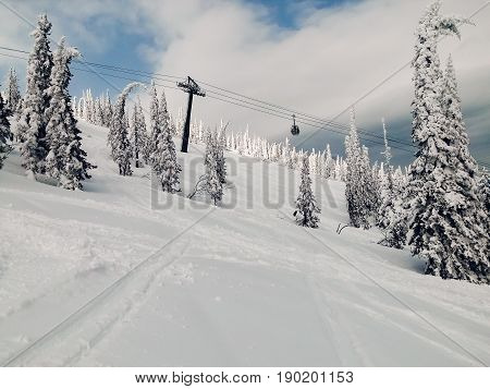 Snowy landscape Sheregesh Kemerovo region ski resort with a cabin lift in the background of mountains. Concept road for downhill skiing and snowboarding.