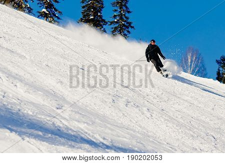Skier mountain skiing riding on track slope. Concept active rest in winter photo in motion snow is scattered. Sheregesh ski resort