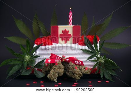 Small infused cake with cannabis nugs, flowers and flag to celebrate candian 150 anniversary and the marijuana industry