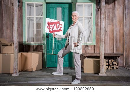 Smiling Senior Woman Standing On Stairs Of New House And Holding Sold Sign