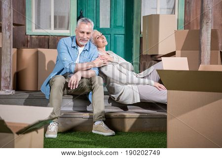 Happy Senior Couple Sitting Together On Stairs Of New House, Relocation Concept