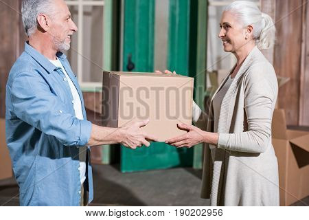 Side View Of Happy Senior Couple Holding Cardboard Box And Smiling Each Other