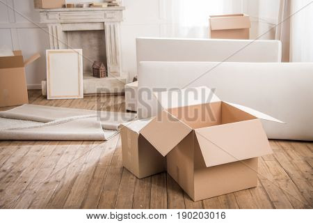 Close-up View Of Cardboard Boxes And Furniture In Empty Room, Relocation Concept