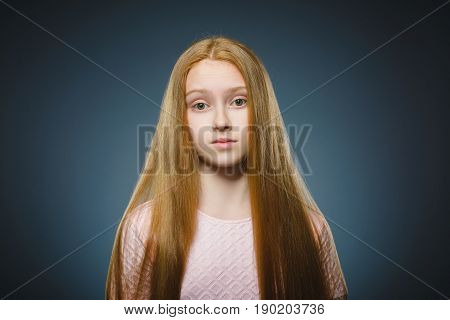Closeup Portrait of handsome girl with astonished expression while standing against grey background.