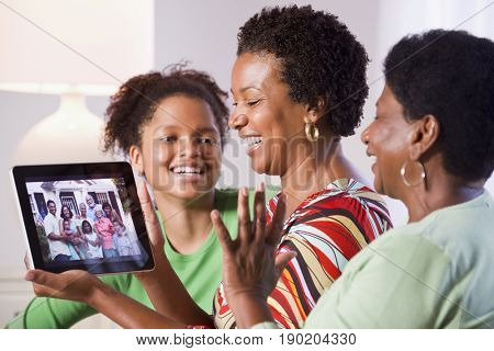 Three generations of Black women talking on tablet computer