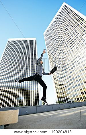 Asian businessman leaping on urban rooftop
