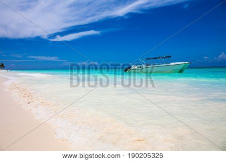 cutter on tropical beach with blue water background