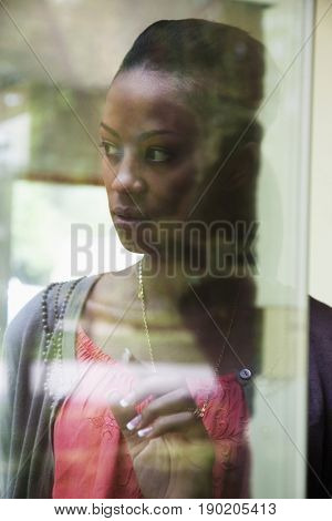 Black woman looking through window
