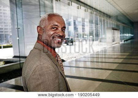 Black businessman smiling in office corridor