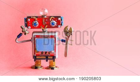 Robot handyman spanner wrench bolt nut in hands. Mechanical cyborg toy, red head, light bulb, monitor body text 1 on blue background. Automation robotic process concept. Pink background, copy space photo