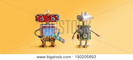 Robots on yellow background. 4th industrial revolution automation concept. Computer service maintenance, repair fix. IT cyber specialist, smiley red head, usb flash stick, quote Hello. Copy space photo