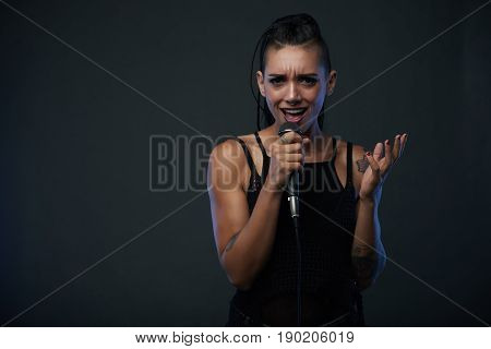 Stylish young woman with tattoos and nose piercing singing a song