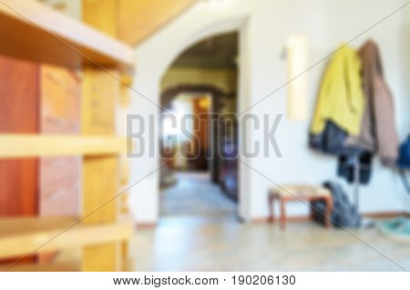 Abstract blur interior with outer clothing on a hanger and open doors for background