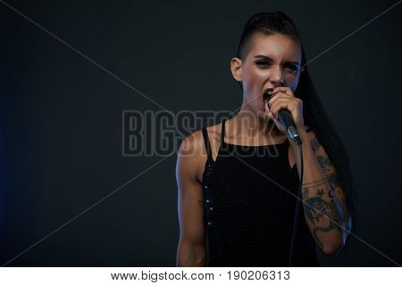 Female rock singer with tattoos and extravagant hair style singing