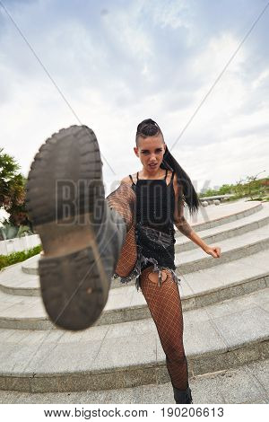 Rebellious young pretty punk girl kicking camera