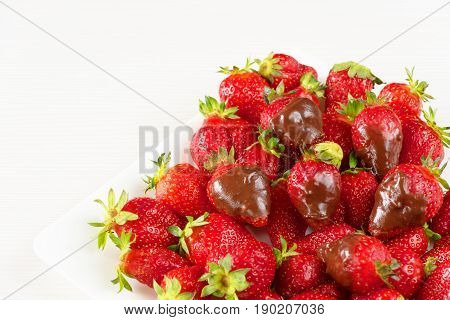 Strawberries dipped in delicious chocolate in white dish isolated on white background. Close up view.