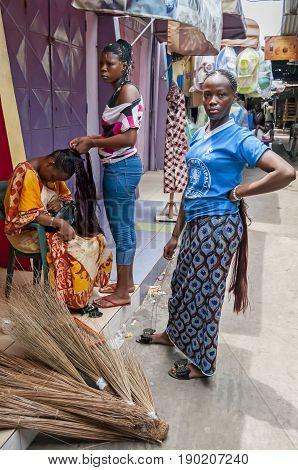 ABIDJAN, IVORY COAST, AFRICA. April 27, 2013. Good looking Ivorian women in the open-air hair salon  in the Abidjan market making African braids stock image.