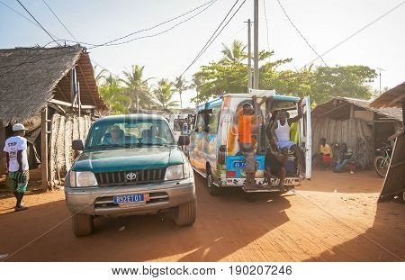 ASSOUINDE, IVORY COAST, AFRICA. April 28, 2013. Busy traffic in the streets of the Assouinde African village. Packed shuttle bus, unsafe ride concept.