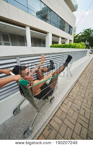 Person pushing shopping cart with cheerful stylish woman in it