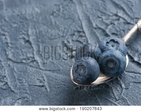 Freshly picked blueberries in spoon closeup. Ripe and juicy fresh blueberries on textured concrete background. Bilberry on dark background with copyspace. Blueberry antioxidant. Healthy eating concept