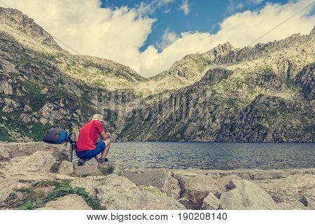 Trekker enjoying crystal clear water. Lake Lambien in Brenta Dolomites, Italy.