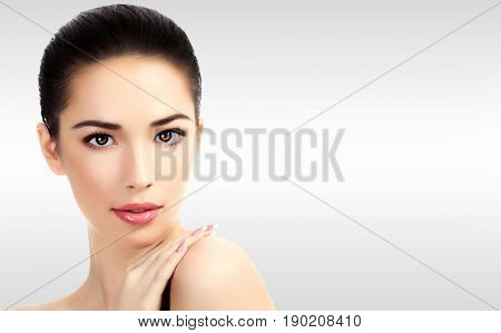 Closeup headshot portrait of a beautiful woman with beauty face and clean smooth soft skin , mild makeup. Grey steel background with a place for your information