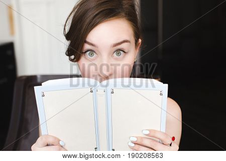 Woman hiding behind the grey book. Woman covering her face. Woman hiding face behind book looking at camera surprise. Education concept. Face expression. Girl holding book.