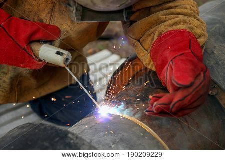 Welding With Sparks. Welder With Protective Equipment Welding Outdoors.