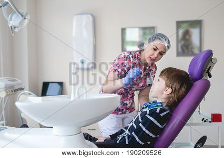 Child as patient with female dentist during dental intervention in dental clinic