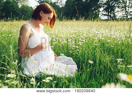 Pregnant woman in white dress on nature outdoors in a meadow. Expectant mother holds hands on belly on the background of chamomile field in park at summer. Pregnancy expectation new life concepts.