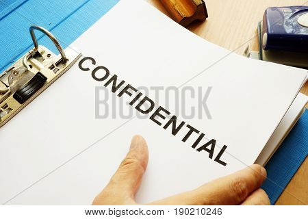 Documents with title Confidential on a table.