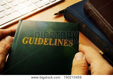 Hands holding A Guidelines in an office.