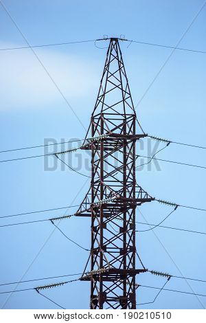 High tension power line electrical wire and big pillar at sunset in Moldova, blue sky