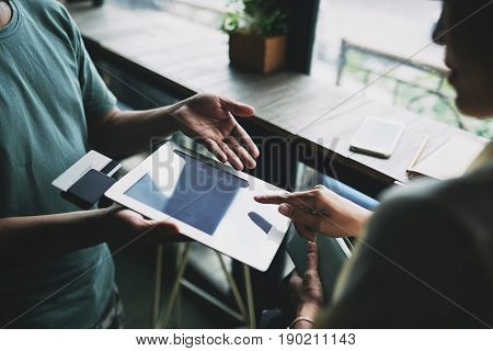 Hands of woman entering information in application on digital tablet to pay for the order