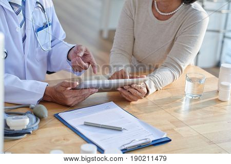 Close-up shot of unrecognizable doctor using digital tablet and discussing records with female patient