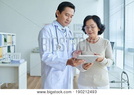 Concentrated Asian cardiologist analyzing electrocardiogram with help of digital tablet, pretty senior patient standing next to him and looking at touchscreen with interest